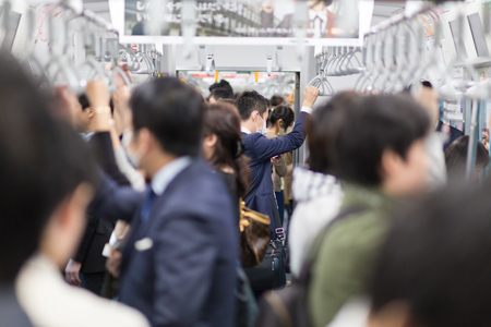 Passengers traveling by Tokyo metro. Business people commuting to work by public transport in rush hour. Shallow depth of field photo. Horizontal composition.