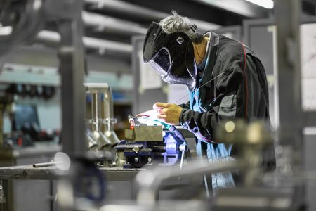 Photo pour Industrial worker with protective mask welding inox elements in steel structures manufacture workshop. - image libre de droit