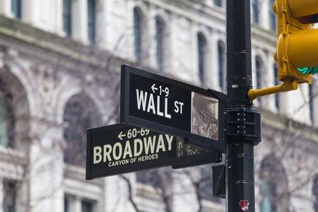 Foto de Wall street sign in New York with American flags and New York Stock Exchange background. - Imagen libre de derechos