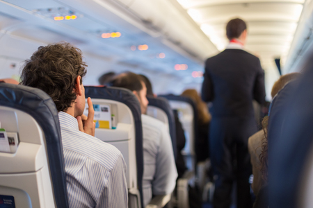 Photo pour Interior of airplane with passengers on seats and steward walking the aisle. - image libre de droit