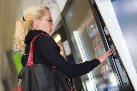 Photo pour Casual caucasian woman using a modern beverage vending machine. Her hand is placed on the dial pad and she is looking on the small display screen. - image libre de droit