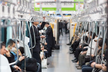 Passengers traveling by Tokyo metro. Business people commuting to work by public transport in rush hour. Shallow depth of field photo.