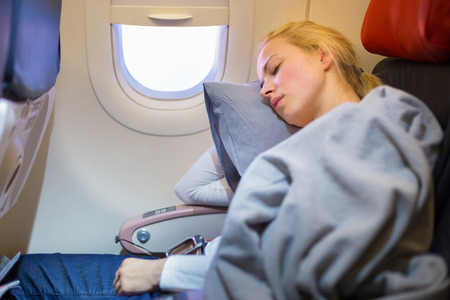 Photo pour Tired blonde casual caucasian lady napping on uncomfortable seat while traveling by airplane. Commercial transportation by planes. - image libre de droit