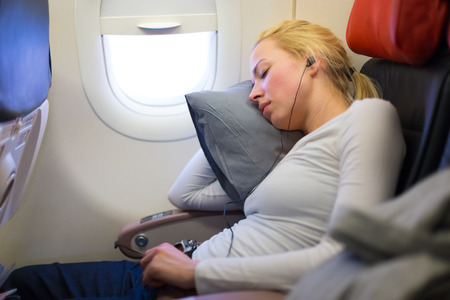 Photo pour Tired blonde casual caucasian lady listens to music while napping on uncomfortable seat while traveling by airplane. Commercial transportation by planes. - image libre de droit