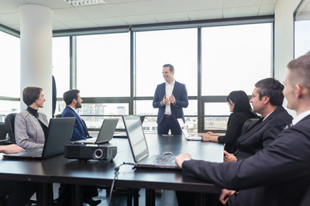Foto per Successful team leader and business owner  leading in-house business meeting, explaining business plans to his employees. Business and entrepreneurship concept. - Immagine Royalty Free