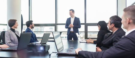 Foto de Successful team leader and business owner leading informal in-house business meeting. Businessman working on laptop in foreground. Business and entrepreneurship concept. - Imagen libre de derechos