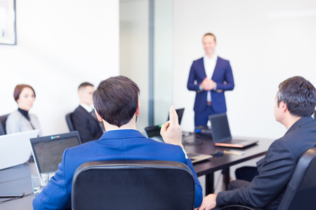 Photo pour Colleague asking a question to  businessman during a presentation. Successful team leader and business owner  leading informal in-house business meeting. Business and entrepreneurship concept. - image libre de droit