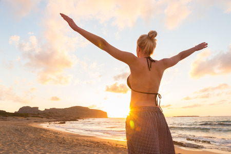 Photo pour Relaxed woman, arms rised, enjoying sun, freedom and life an beautiful beach in sunset. Young lady feeling free, relaxed and happy. Concept of vacations, freedom, happiness, enjoyment and well being. - image libre de droit