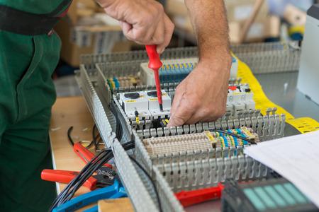 Photo pour Electrician assembling industrial electric cabinet in workshop. - image libre de droit