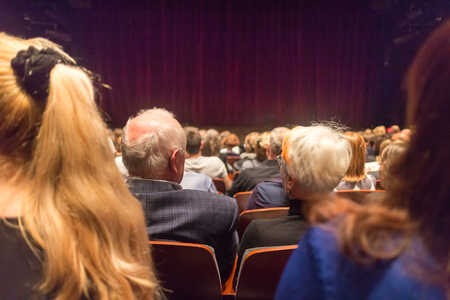 Photo pour Audience in theathre waiting for drama play to start sen from the rear. - image libre de droit