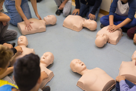 Photo pour First aid cardiopulmonary resuscitation course in primary school. Kids practicing on resuscitation dolls. - image libre de droit