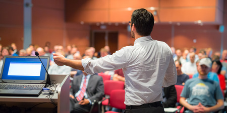 Foto per Speaker giving a talk on corporate Business Conference. Audience at the conference hall. Business and Entrepreneurship event. Panoramic composition. - Immagine Royalty Free