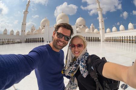 Foto de Tourist couple taking selfie in the courtyard of famous Sheikh Zayed Grand Mosque in Abu Dhabi, United Arab Emirates. - Imagen libre de derechos