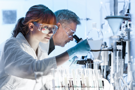 Photo pour Health care researchers working in life science laboratory. Young female research scientist and senior male supervisor preparing and analyzing microscope slides in research lab. - image libre de droit