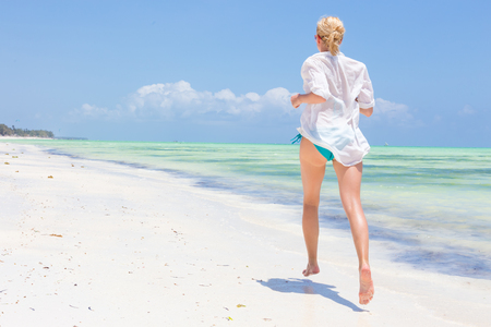 Happy woman having fun, enjoying summer, running joyfully on tropical beach. Beautiful caucasian model wearing white beach tunic on vacations on picture perfect Paje beach, Zanzibar, Tanzania.