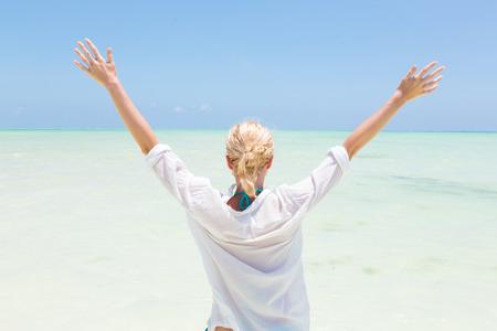 Happy woman, arms rised, enjoying, relaxing joyfully in summer at white tropical beach. Beautiful caucasian model wearing white beach tunic on vacations on Paje beach, Zanzibar, Tanzania.