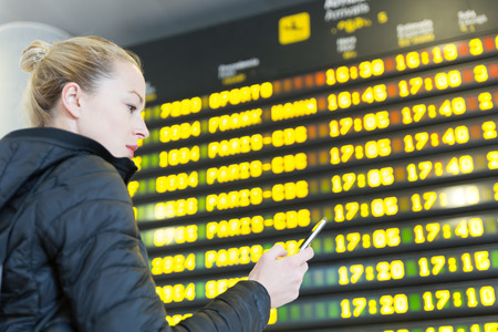 Young woman at international airport looking at the flight information board, holding smart phone in her hand, checking flight informations on phone application.