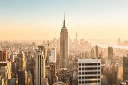 Foto de New York City. Manhattan downtown skyline with illuminated Empire State Building and skyscrapers at amazing golden sunset. USA. - Imagen libre de derechos