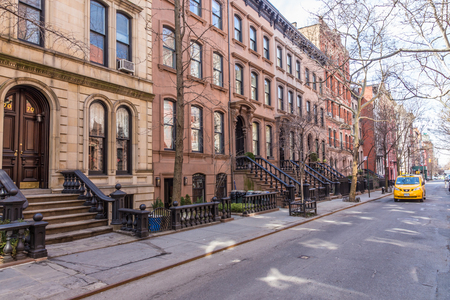 Scenic tree lined street of historic brownstone buildings in the West Village neighborhood of Manhattan in New York City, NYC USA. Traditional yellow taxi car driving along street.