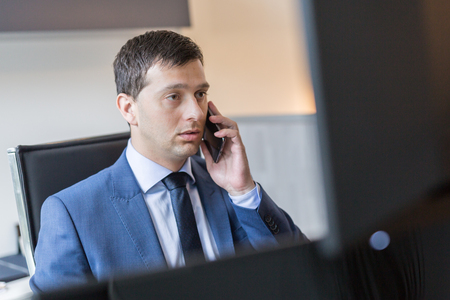 Male stock broker talking on mobile phone while watching charts and data analyses on multiple computer screens.