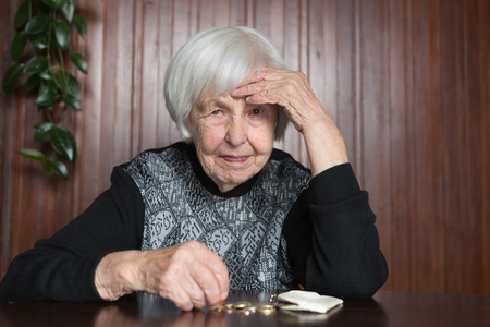 Photo pour Elderly 95 years old woman sitting miserably at the table at home and counting remaining coins from the pension in her wallet after paying the bills. - image libre de droit