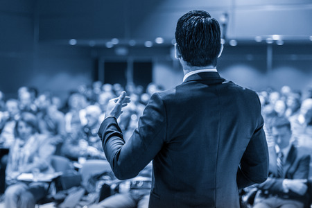 Foto de Speaker giving a talk on corporate business conference. Unrecognizable people in audience at conference hall. Business and Entrepreneurship event. Blue toned grayscale image. - Imagen libre de derechos