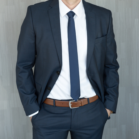 Photo for Torso of anonymous white collar worker standing with hands in pockets, wearing beautiful fashionable classic navy blue suit against grey backgound. - Royalty Free Image