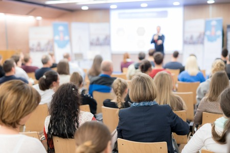 Photo pour Speaker giving a talk in conference hall at business event. Audience at the conference hall. Business and Entrepreneurship concept. Focus on unrecognizable people in audience. - image libre de droit