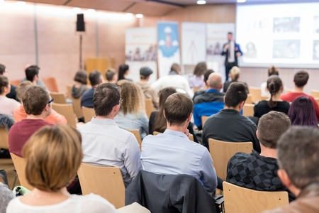 Foto de Speaker giving a talk in conference hall at business event. Audience at the conference hall. Business and Entrepreneurship concept. Focus on unrecognizable people in audience. - Imagen libre de derechos