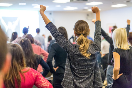 Photo pour Life coaching symposium. Speaker giving interactive motivational speech at business workshop. Rear view of unrecognizable participants feeling empowered and motivated, hands raised high in air. - image libre de droit