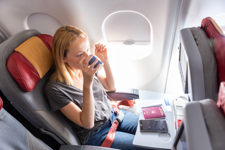 Photo pour Woman on commercial passengers airplane during flight. Female traveler seated in passanger cabin drinking coffee. Sun shining trough airplane window. - image libre de droit