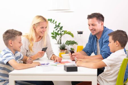 Photo pour Happy young family playing card game at dining table at bright modern home. Spending quality leisure time with children and family concept. Cards are generic and debranded. - image libre de droit