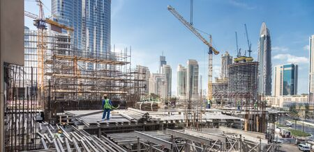 Photo pour Laborers working on modern constraction site works in Dubai. Fast urban development consept. - image libre de droit