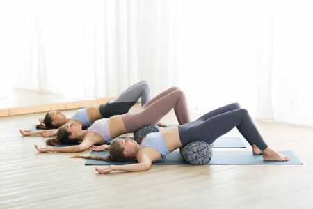 Foto de Restorative yoga with a bolster. Group of three young sporty attractive women in yoga studio, lying on bolster cushion, stretching and relaxing during restorative yoga. Healthy active lifestyle. - Imagen libre de derechos