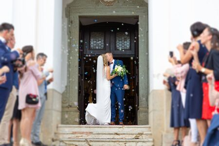 Foto de Newlyweds kissing while exiting the church after wedding ceremony, family and friends celebrating their love with the shower of soap bubbles, custom undermining traditional rice bath. - Imagen libre de derechos