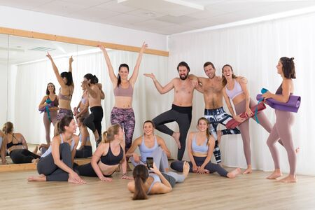 Photo for Group of young authentic real sporty attractive people in yoga studio having fun relaxing and socializing after hot yoga class. Healthy active lifestyle, working out in gym. - Royalty Free Image