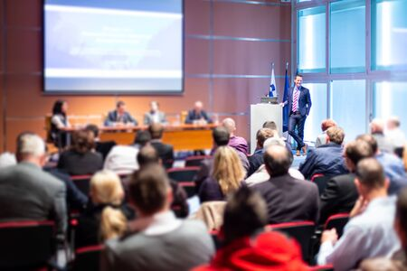 Photo pour Business and entrepreneurship symposium. Speaker giving a talk at business meeting. Audience in conference hall. Rear view of unrecognized participant in audience. - image libre de droit