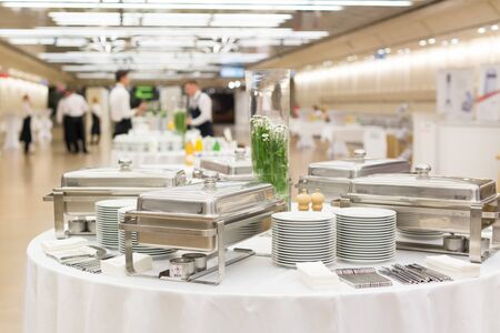 Photo pour Waiters prepare buffet before a coffee break at business conference meeting. - image libre de droit