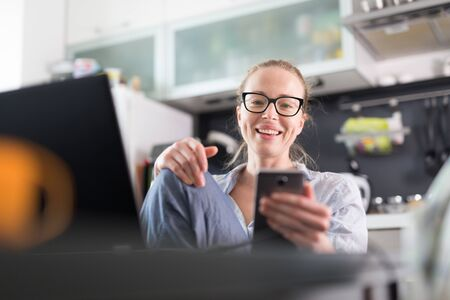 Photo pour Stay at home and social distancing. Woman in her casual home clothing working remotly from kitchen dining table. Video chatting using social media with friend, family, business clients or partners. - image libre de droit