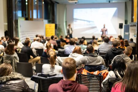 Photo pour Speaker giving a talk in conference hall at business event. Rear view of unrecognizable people in audience at the conference hall. Business and entrepreneurship concept. - image libre de droit