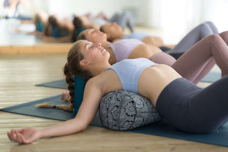 Photo for Restorative yoga with a bolster. Group of three young sporty attractive women in yoga studio, lying on bolster cushion, stretching and relaxing during restorative yoga. Healthy active lifestyle - Royalty Free Image