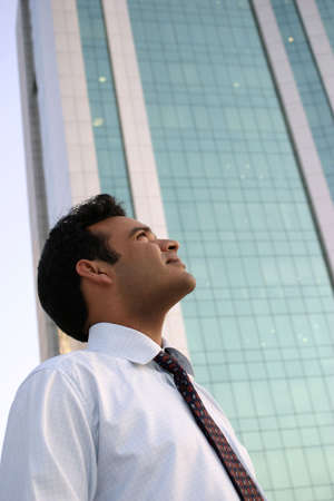Young Man Looking Up at a highrise building with dreams in his eyes