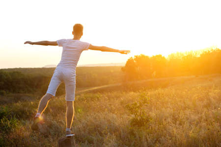 Foto per A young boy, dressed in a light T-shirt and shorts, with open arms against the setting sun. Fantastic sunset and beautiful sky in the background. Active life concept. - Immagine Royalty Free