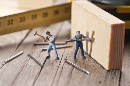 Two workers sticks nail. The concept of teamwork.