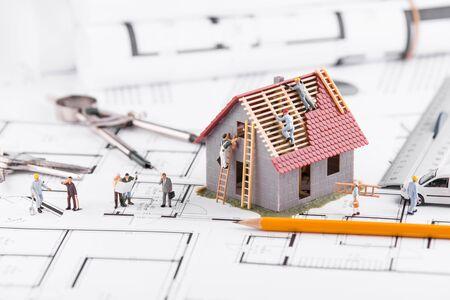 Photo pour Tiny people build houses for architectural plans. The concept of teamwork. - image libre de droit