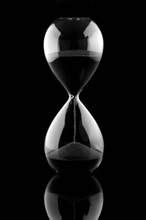 Photo pour Sand running through the bulbs of an hourglass measuring the passing time in a countdown to a deadline, on a dark background with copyspace - image libre de droit