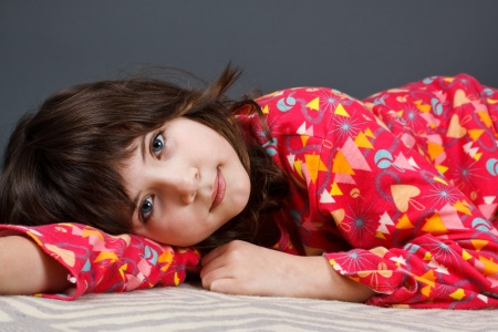 A cute 9-year-old girl lying in colourful pyjamas, looking into camera - grey background