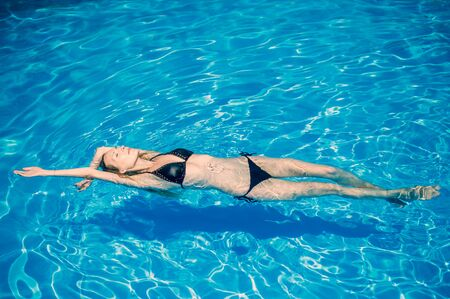 Photo pour Young slender woman in a black bikini swimsuit relaxes on the surface of the water in the pool and rests - image libre de droit