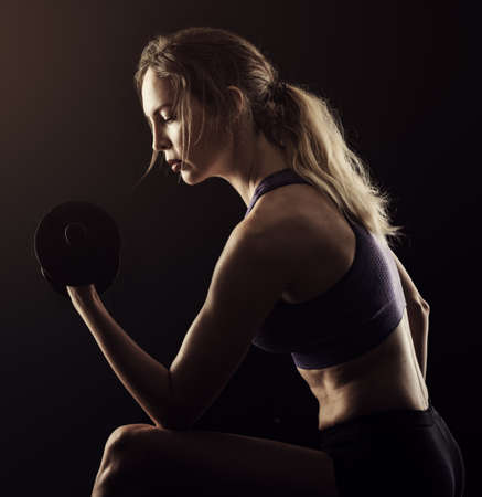 Photo for Slim athletic woman Holding dumbbell in the hand on black - Royalty Free Image