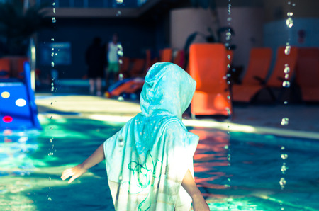 little girl in towel with cape in the indoor swimming pool back view